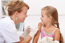 Schulärztin mit Mädchen beim Impfen